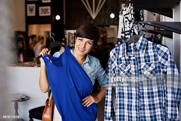 Portrait of woman trying dress in fashion store