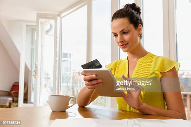 Portrait of woman using digital tablet and credit card in office