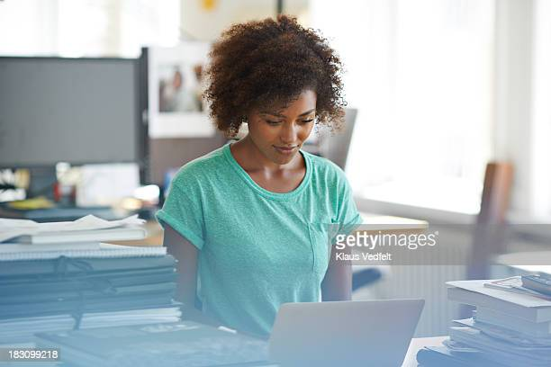 Portrait of woman using laptop at office