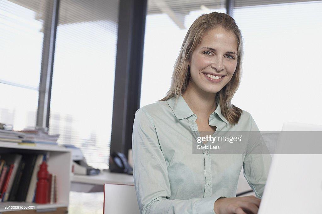 Portrait of woman using laptop in office : Stockfoto