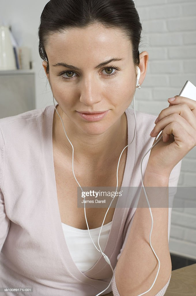 Portrait of woman using mp3 player at home : Stockfoto