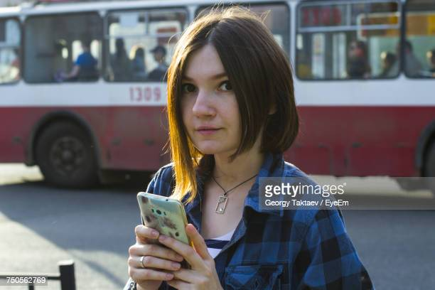 Portrait Of Woman Using Phone On Road Against Bus