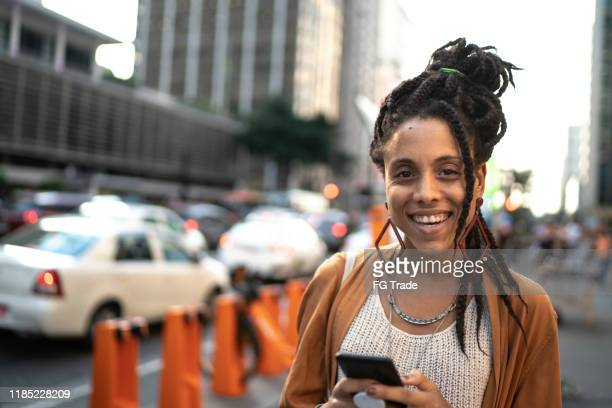 portrait of woman using smartphone - locs hairstyle stock pictures, royalty-free photos & images