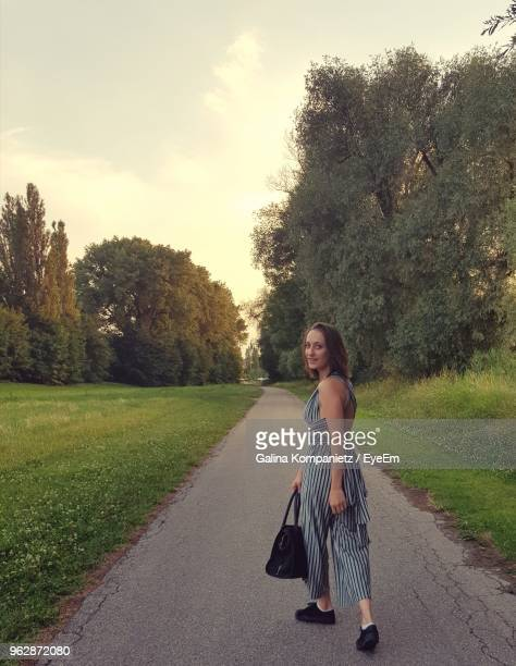 portrait of woman walking on road against trees - straubing stock pictures, royalty-free photos & images