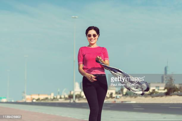 portrait of woman walking on sidewalk in city against sky - aikāne stock pictures, royalty-free photos & images