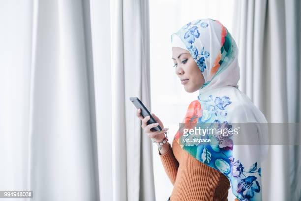 彼女のスマート フォンを使用してカラフルなヒジャーブを着ている女性の肖像画。 - 宗教的なベール ストックフォトと画像