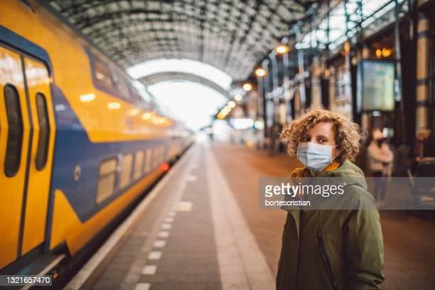portrait of woman wearing a mask standing at railroad station - bortes stock-fotos und bilder