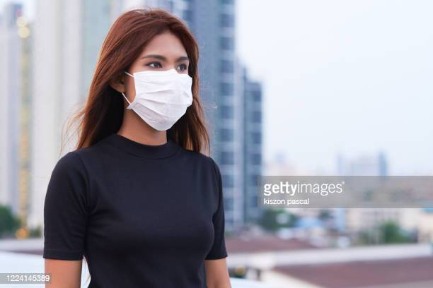 portrait of woman wearing a medical mask in the city . epidemic prevention , pollution and allergy - parte del cuerpo humano fotografías e imágenes de stock