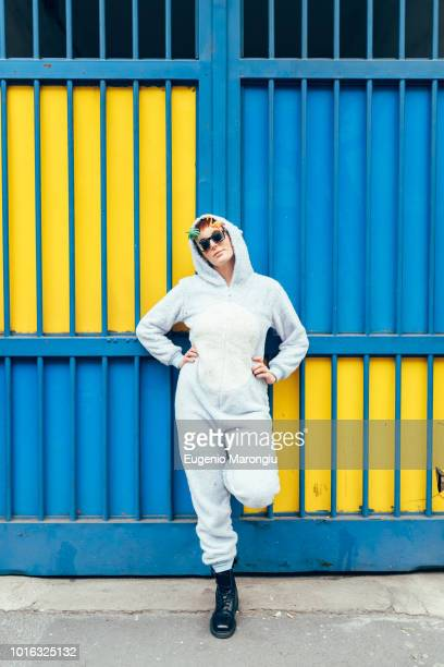 portrait of woman wearing adult bodysuit, hands on hips looking at camera - white jumpsuit stock pictures, royalty-free photos & images