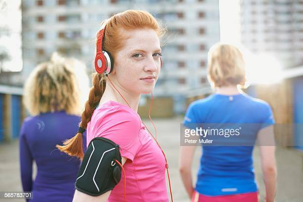Portrait of woman wearing armband and headphones before exercise looking over shoulder at camera