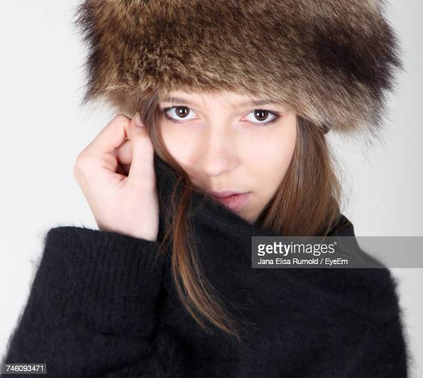 portrait of woman wearing black sweater and brown fur hat against white background - fur hat stock photos and pictures