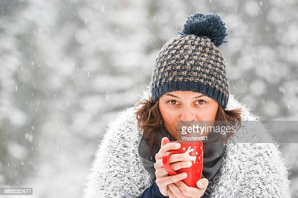 Portrait of woman wearing bobble hat holding cup with hot beverage in winter