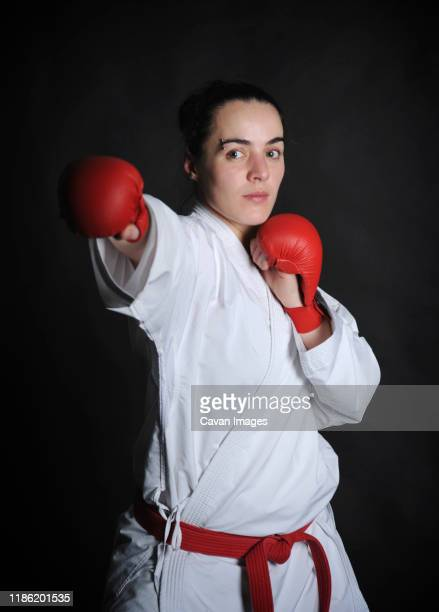 portrait of woman wearing boxing gloves while practicing karate against black background - boxing belt stock pictures, royalty-free photos & images