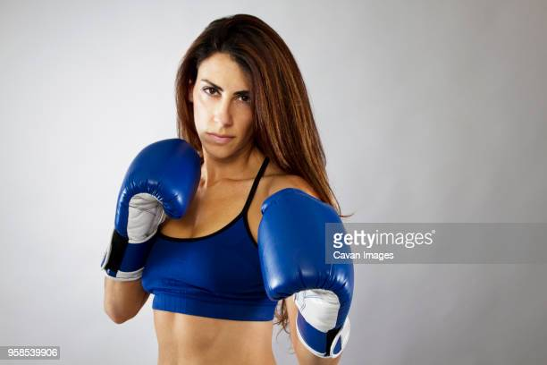 Portrait of woman wearing boxing gloves while standing against gray background