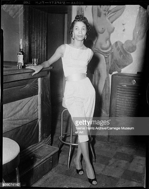 Portrait of woman wearing capri pants and halter top in bar with painting of nude in background circa 19481965