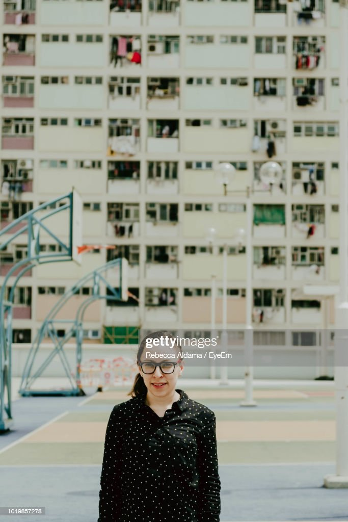 Portrait Of Woman Wearing Eyeglasses While Standing Against Building During Sunny Day : Stock Photo