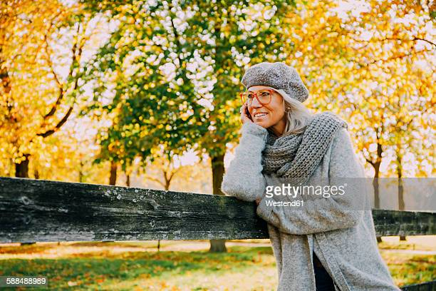 Portrait of woman wearing grey knitwear in an autumnal park