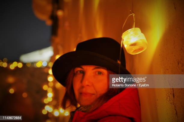 Portrait Of Woman Wearing Hat Against Illuminated Light At Night