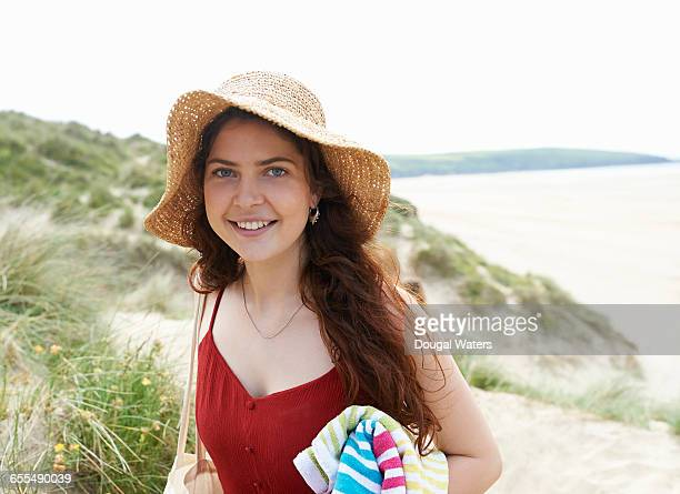 Portrait of woman wearing hat at beach.