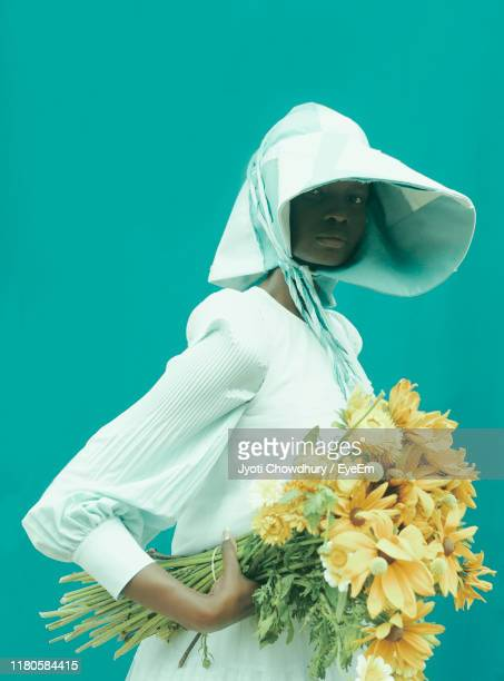 portrait of woman wearing hat holding flowers against blue background - art bildbanksfoton och bilder
