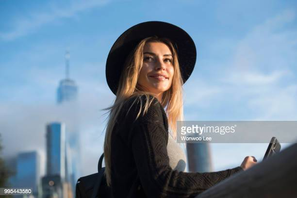 portrait of woman wearing hat looking away smiling, new york, usa - 世界的な名所 ストックフォトと画像