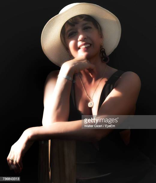 Portrait Of Woman Wearing Hat While Leaning On Wooden Post
