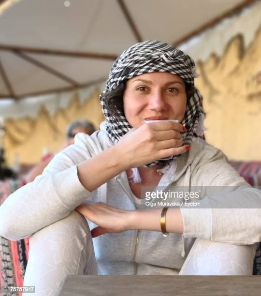 portrait of woman wearing headscarf while having drink at table - bedouin stock pictures, royalty-free photos & images
