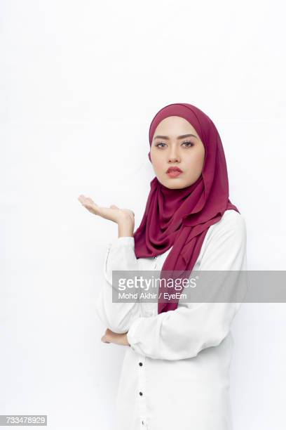 Portrait Of Woman Wearing Hijab Standing Against White Background
