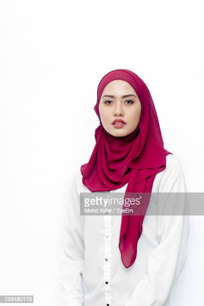 portrait of woman wearing hijab standing against white background - hijab - fotografias e filmes do acervo