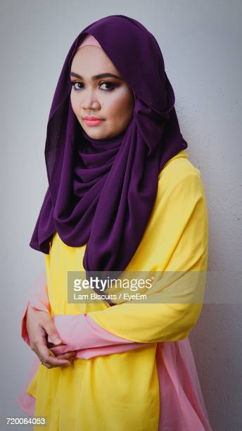 Portrait Of Woman Wearing Hijab Standing Against White Wall