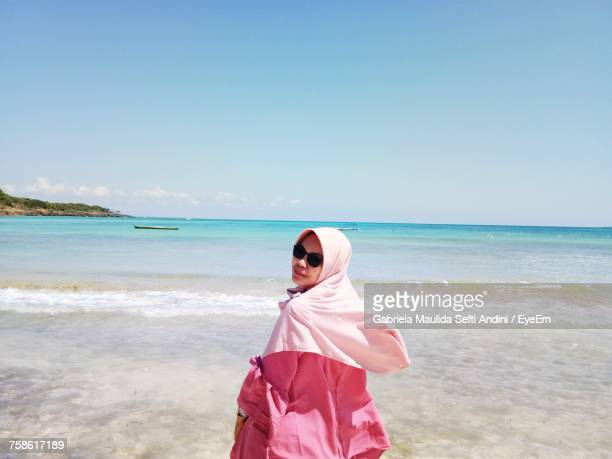 portrait of woman wearing hijab standing at beach against sky during sunny day - muslim woman beach stock photos and pictures