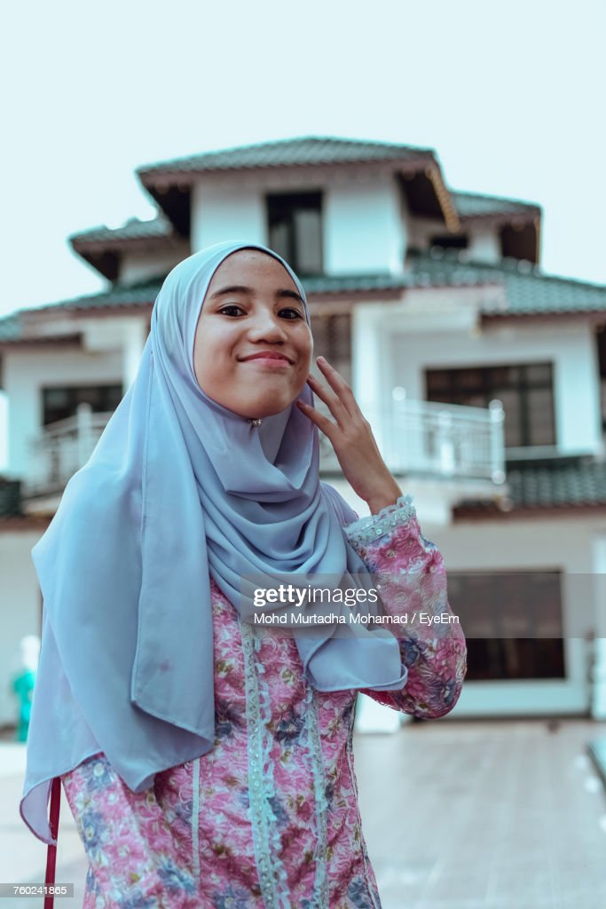 Portrait Of Woman Wearing Hijab While Standing Against House : Stock Photo
