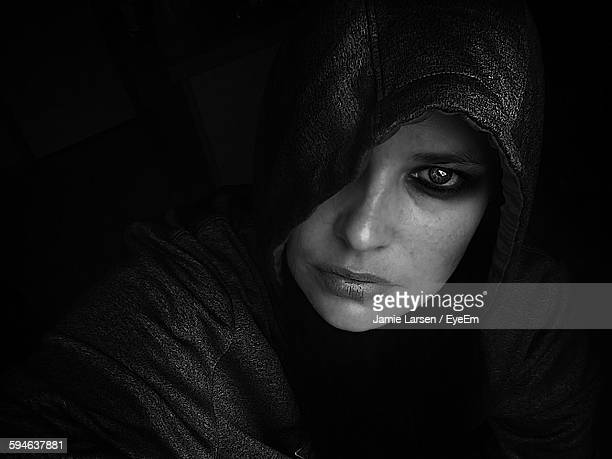Portrait Of Woman Wearing Hooded Shirt Against Black Background