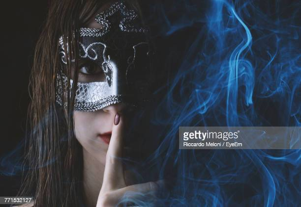 portrait of woman wearing mask against black background - black mask disguise stock pictures, royalty-free photos & images