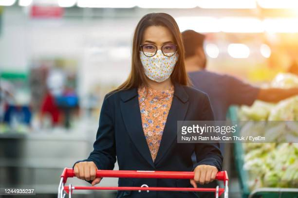 portrait of woman wearing mask holding shopping cart in store - obscured face stock pictures, royalty-free photos & images