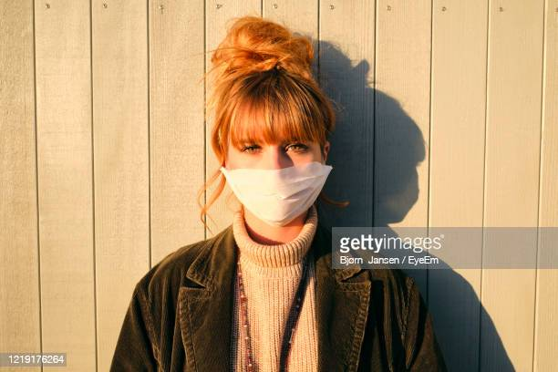 portrait of woman wearing mask standing against wall - obscured face stock pictures, royalty-free photos & images