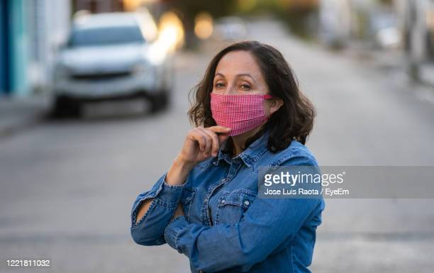 portrait of woman wearing mask standing on street - masque tissus photos et images de collection