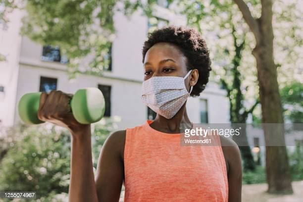 portrait of woman wearing protective mask exercising with dumbbell outdoors - face guard sport stock pictures, royalty-free photos & images