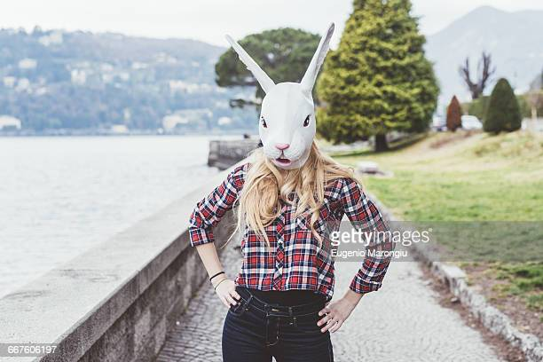 portrait of woman wearing rabbit mask with hands on hips, lake como, italy - rabbit mask stock pictures, royalty-free photos & images