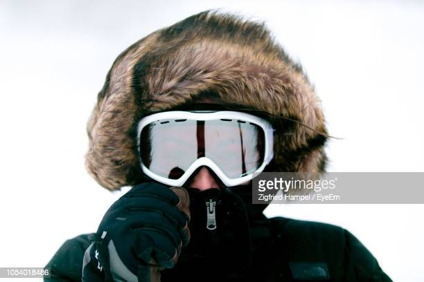 portrait of woman wearing ski goggles against clear sky - ski goggles stock pictures, royalty-free photos & images