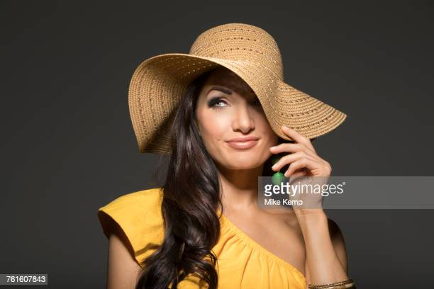 portrait of woman wearing straw hat and yellow top - earring stock pictures, royalty-free photos & images