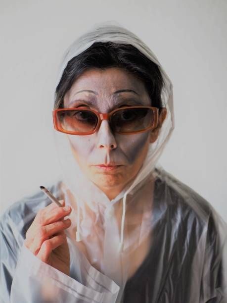 Portrait Of Woman Wearing Sunglasses Holding Cigarette Against White Background
