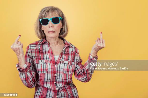 portrait of woman wearing sunglasses while showing obscene gesture against yellow background - dito medio foto e immagini stock