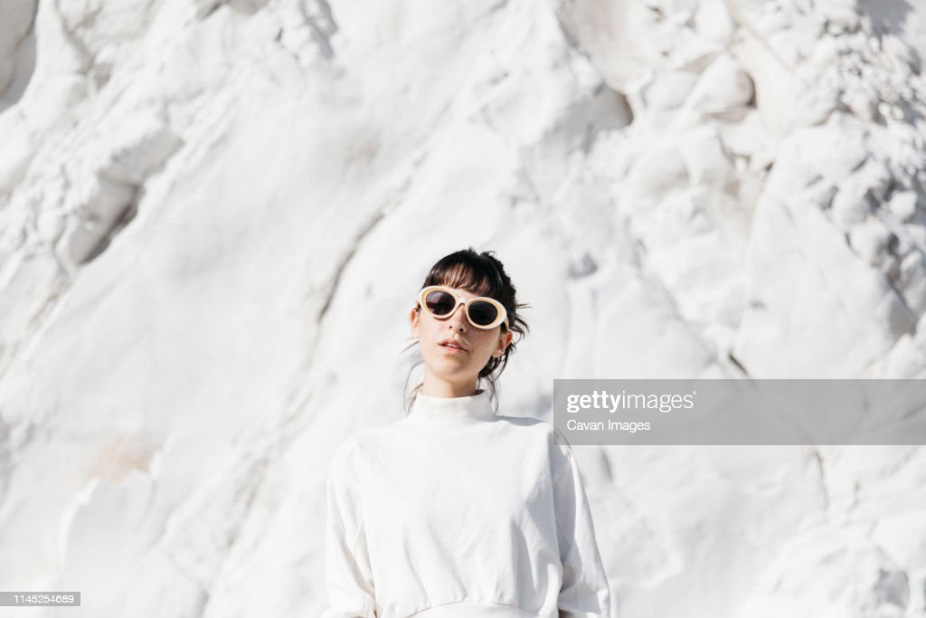 Portrait of woman wearing sunglasses while standing against snow covered rock during sunny day : Stock Photo