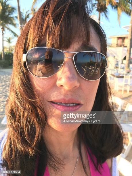 Portrait Of Woman Wearing Sunglasses While Standing At Beach