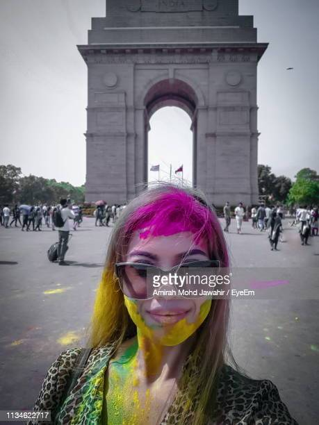 Portrait Of Woman Wearing Sunglasses With Face Paint While Standing Against India Gate