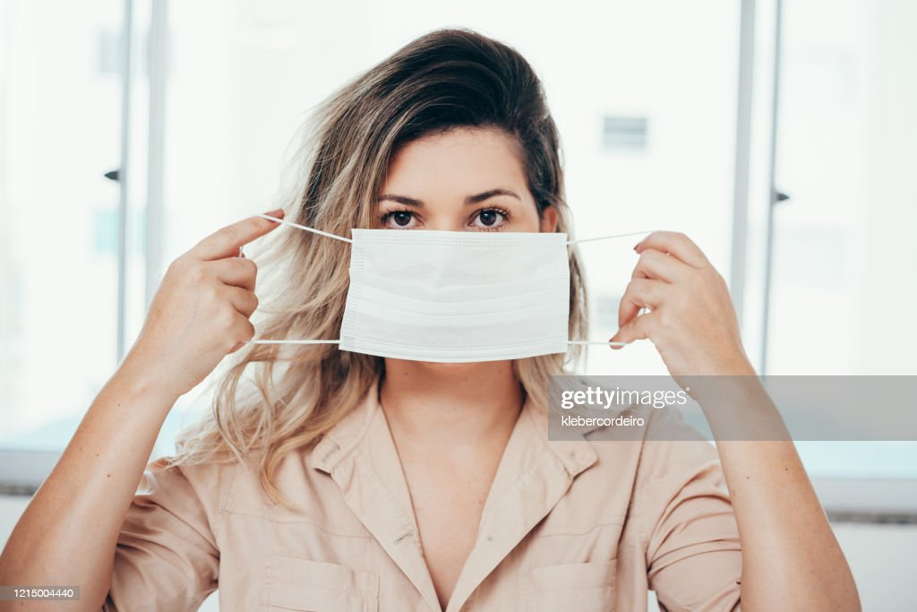 Portrait of woman wearing surgical mask at home. Covid-19, coronavirus and quarantine concept. : Stock Photo