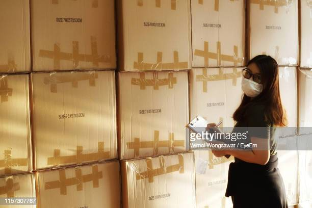 portrait of woman wearing surgical mask while checking stock in warehouse - wimol wongsawat stock photos and pictures