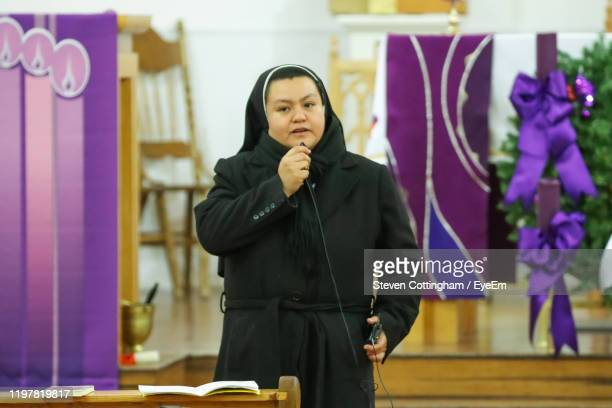 portrait of woman wearing traditional clothing giving speech in church - steven cottingham stock-fotos und bilder