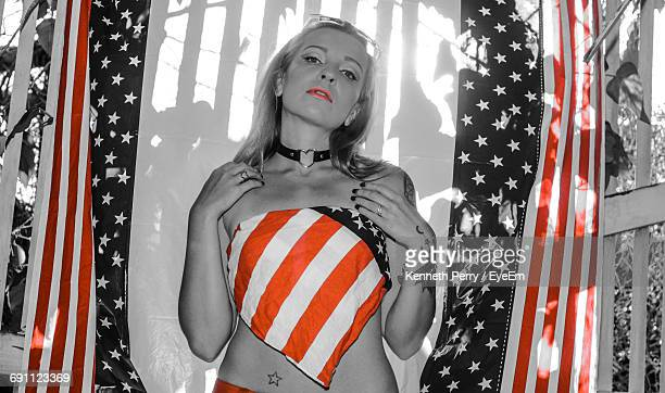 portrait of woman wearing tube top while standing against american flag - red tube top stock photos and pictures